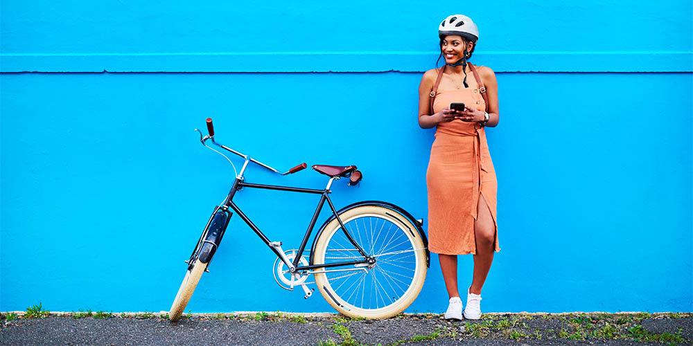 Fille debout à côté de son vélo contre un mur bleu.