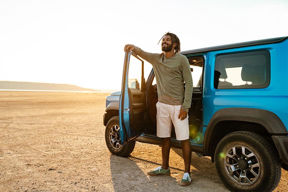 Man die uit zijn blauwe tereinwagen stapt en over een zanderige omgeving kijkt